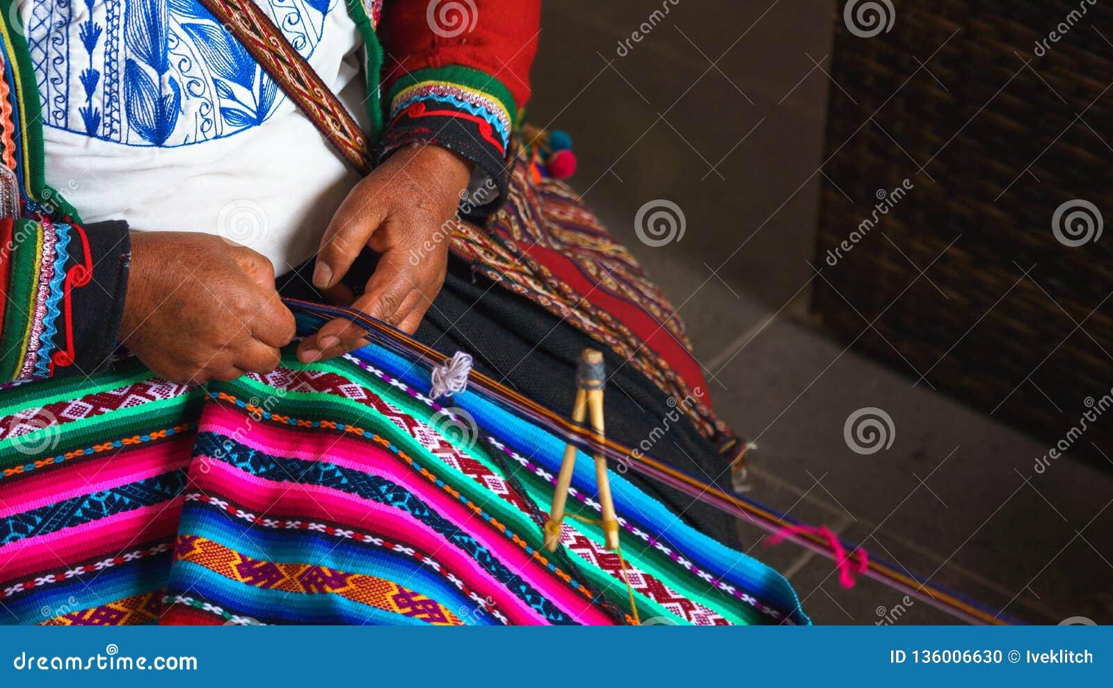 关闭编织在秘鲁 cusco秘鲁 在五颜六色的传统当地秘鲁结束打扮的妇女编织一张地毯与