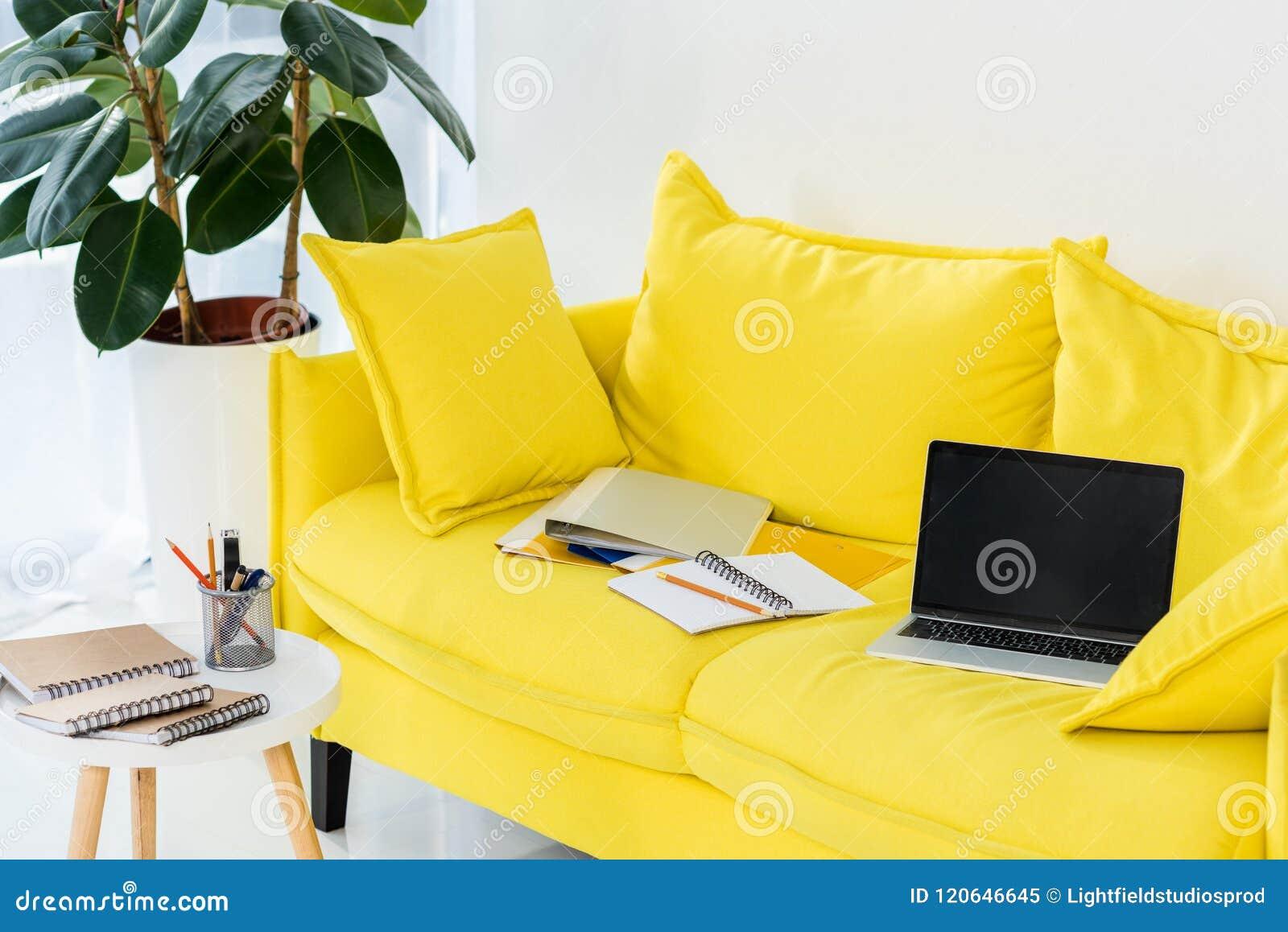 关闭膝上型计算机、笔记本和文件夹看法在黄色沙发