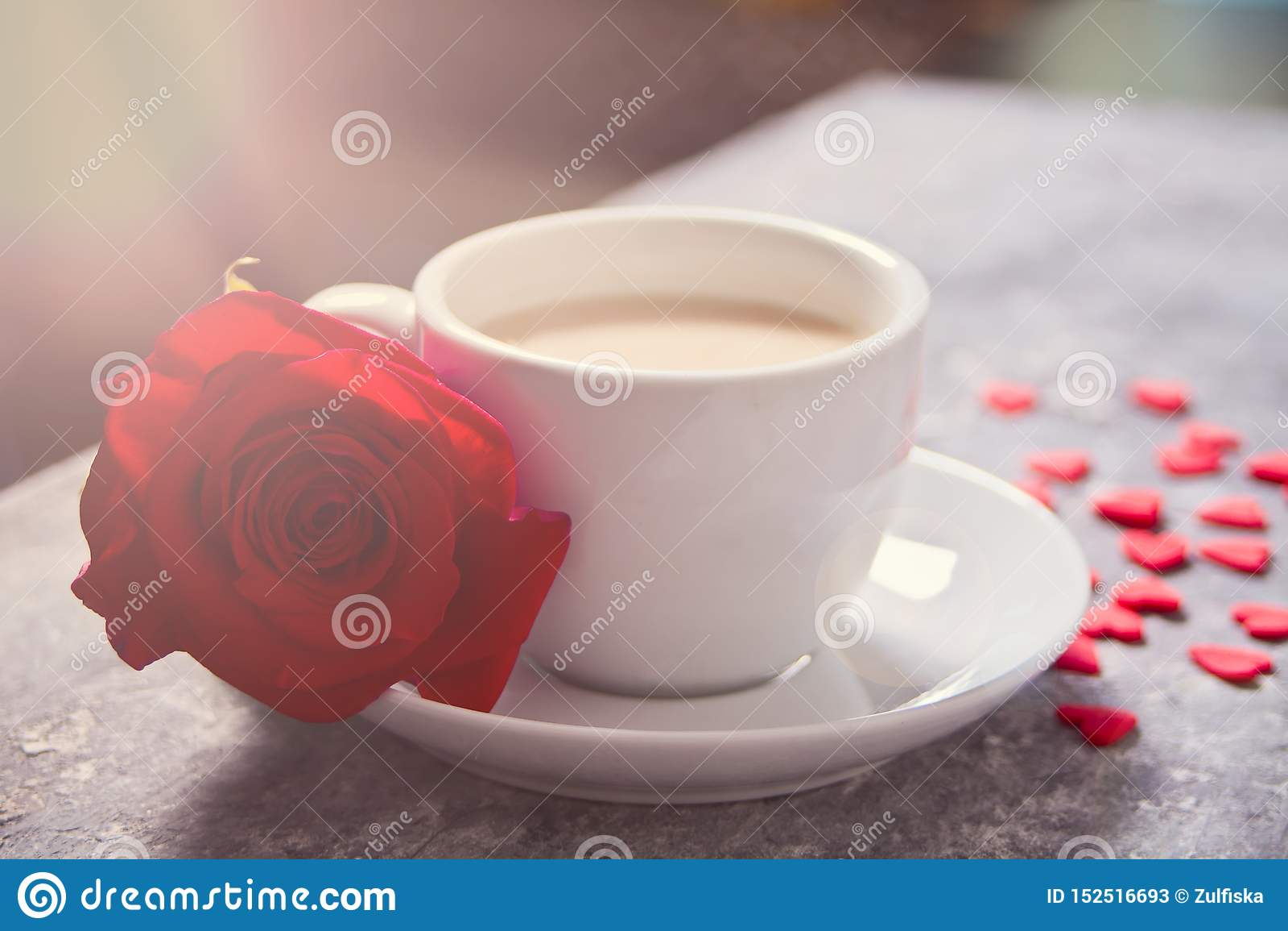 关闭茶与红色玫瑰的和在桌上的小糖果心脏