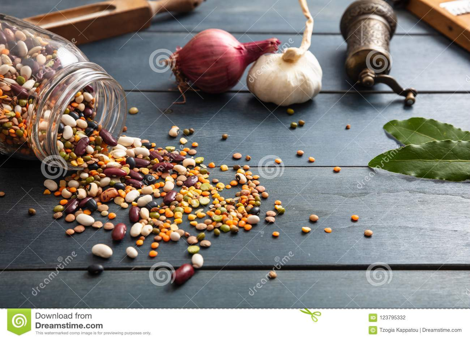 关闭豆类的分类在一个玻璃瓶子的,溢出在一个木桌面背景、胡椒研磨机、葱、大蒜和花格