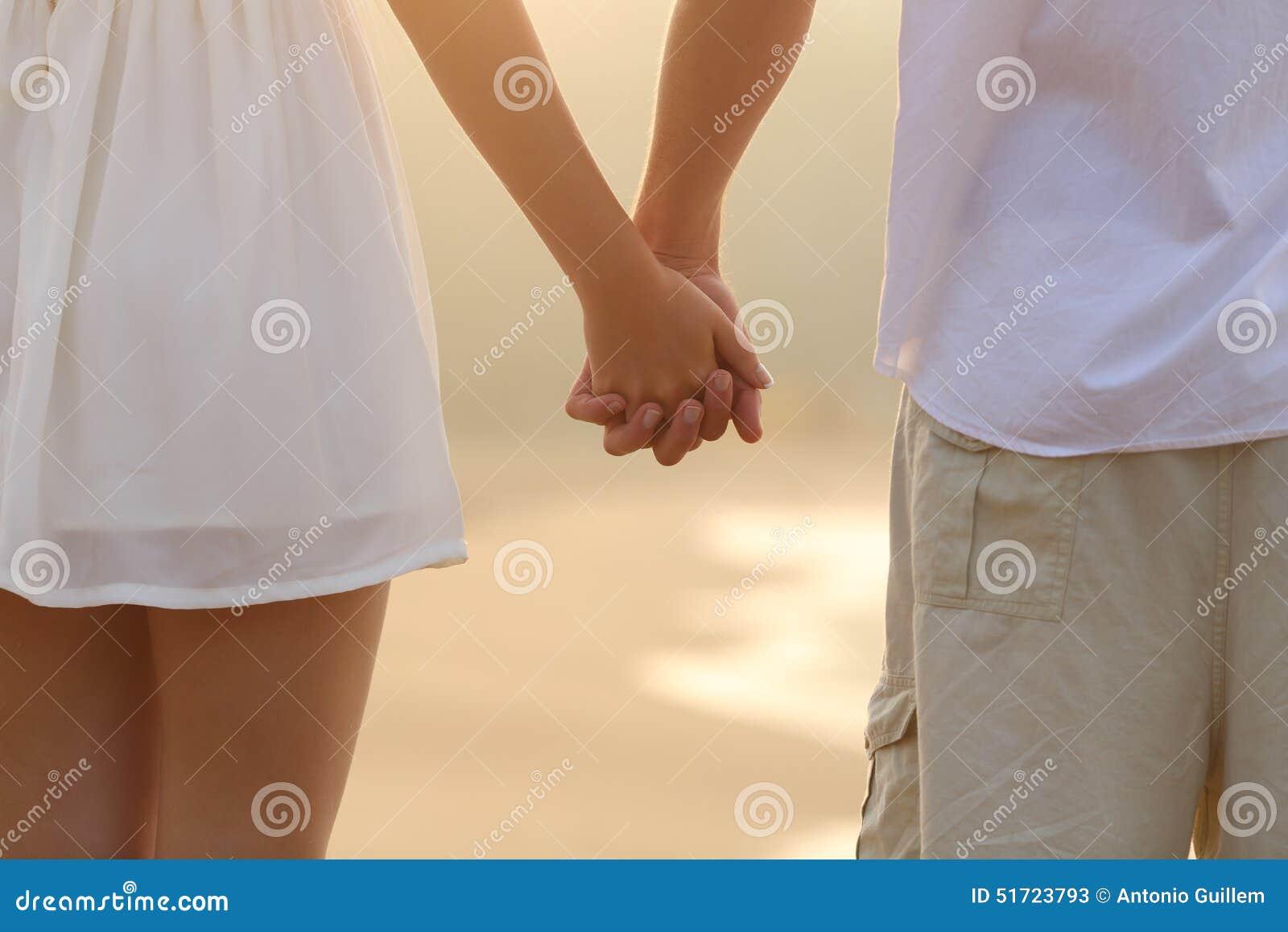 关闭走和握在海滩的夫妇手