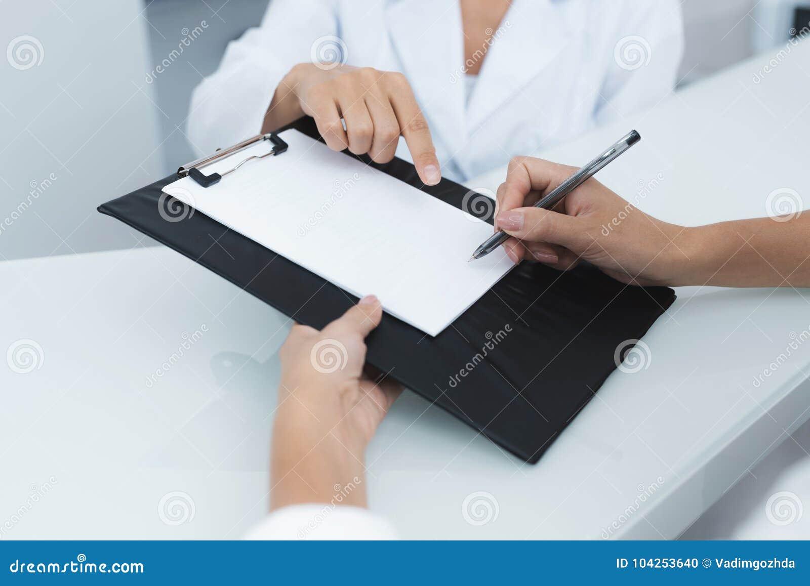 关闭 一家诊所的秘书帮助耐心在开始治疗前填好必要的形式