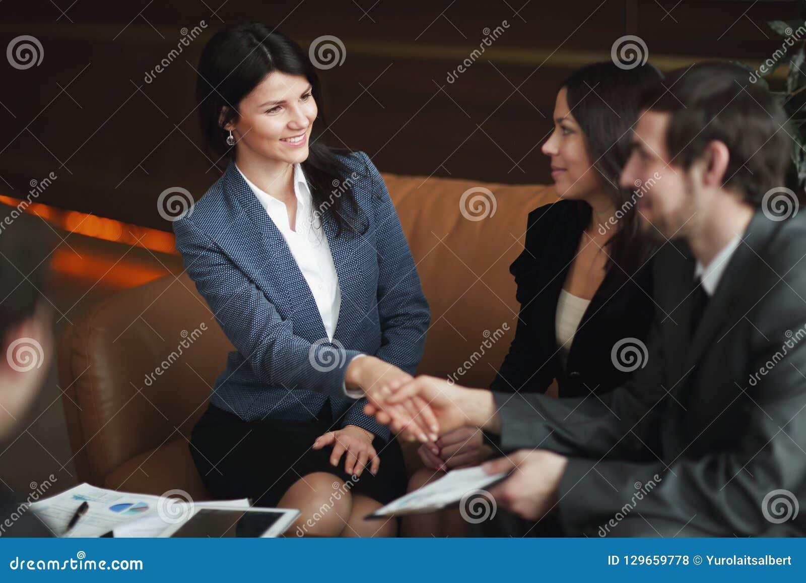 关闭 女商人与坐在工作书桌的商务伙伴握手