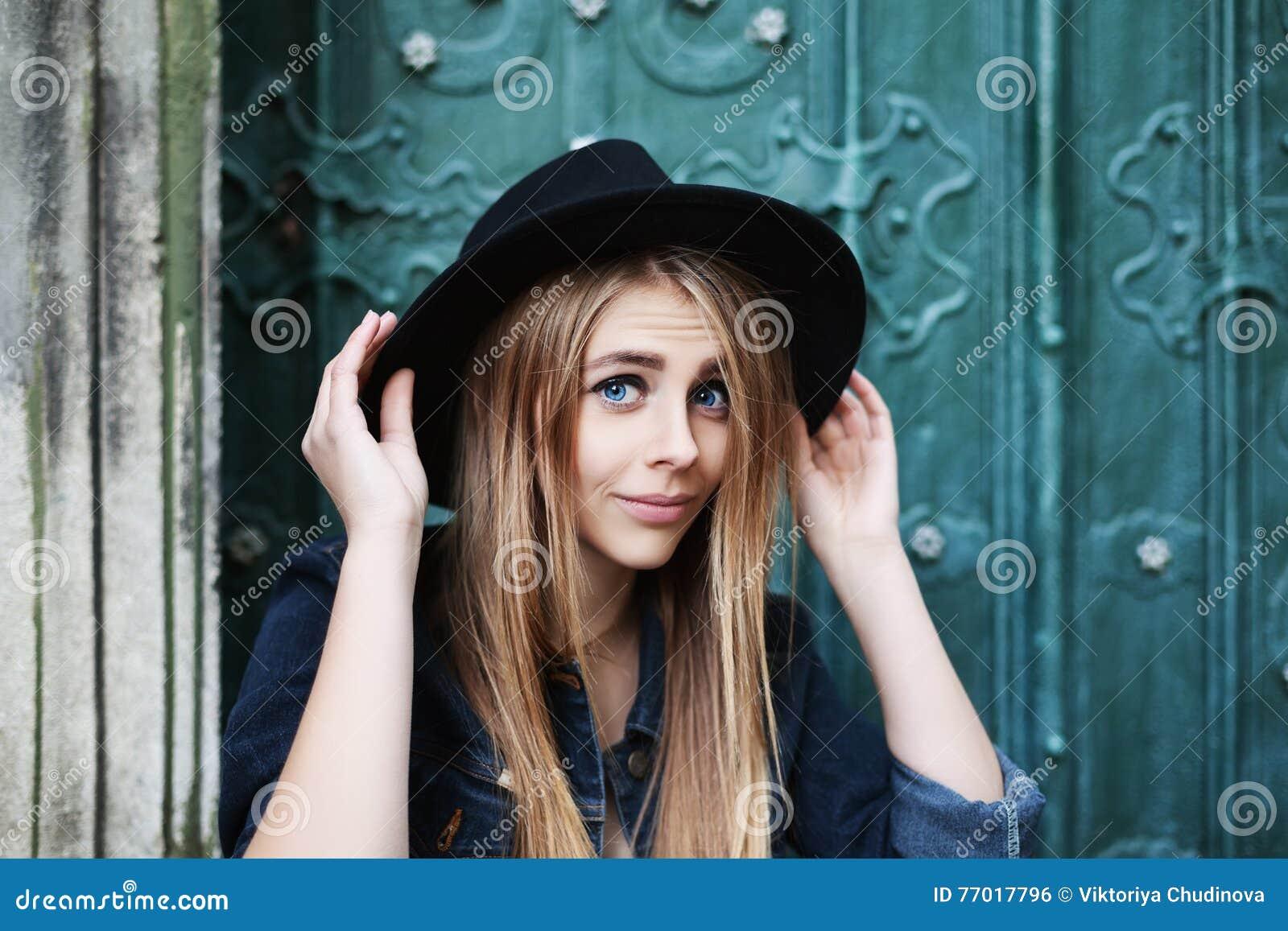 关闭戴时髦的宽充满的黑帽会议的美丽的嬉戏的微笑的女孩画象  式样看的照相机