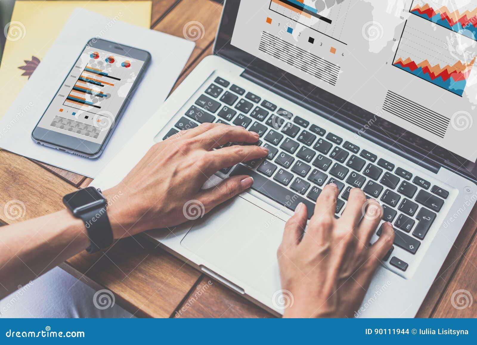 其次在木桌有图表、图和图的智能手机在屏幕上 在网上学会的学生