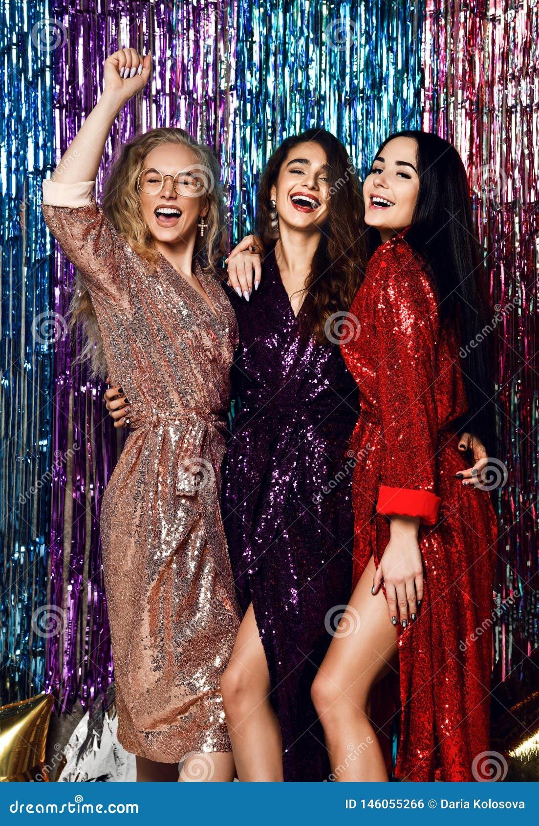 典雅的成套装备的庆祝新年的三名美丽的时髦的妇女的疯狂的党时间,生日,获得乐趣,跳舞