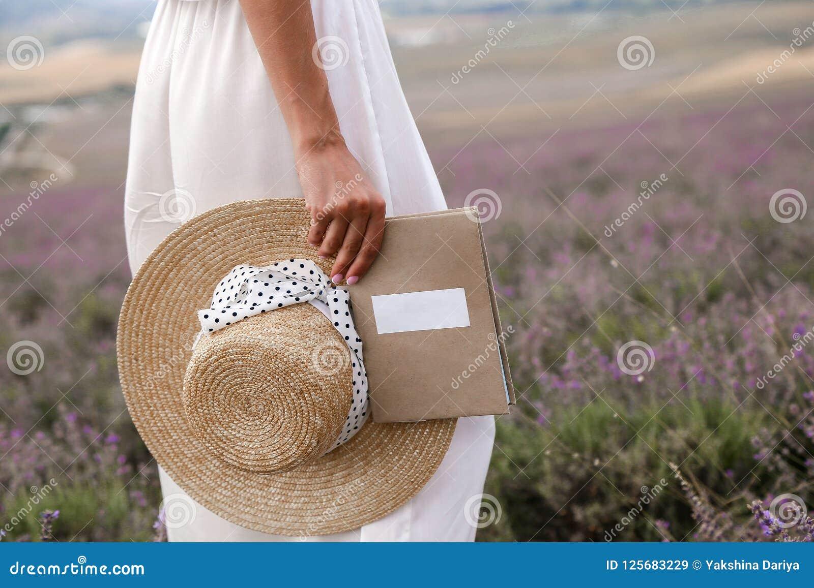 典雅的白色摆在普罗旺斯la的礼服和草帽的妇女