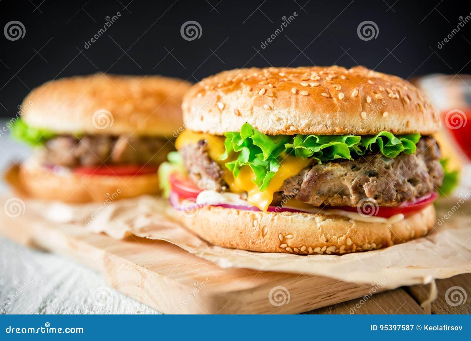 经典鲜美汉堡包用鲜美牛肉和调味汁在黑暗的背景 美国食物