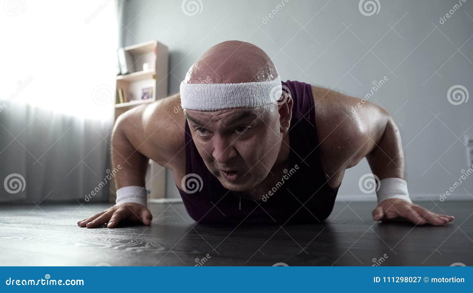 冒汗与设法微弱的胳膊的肌肉的男性在家做俯卧撑,锻炼