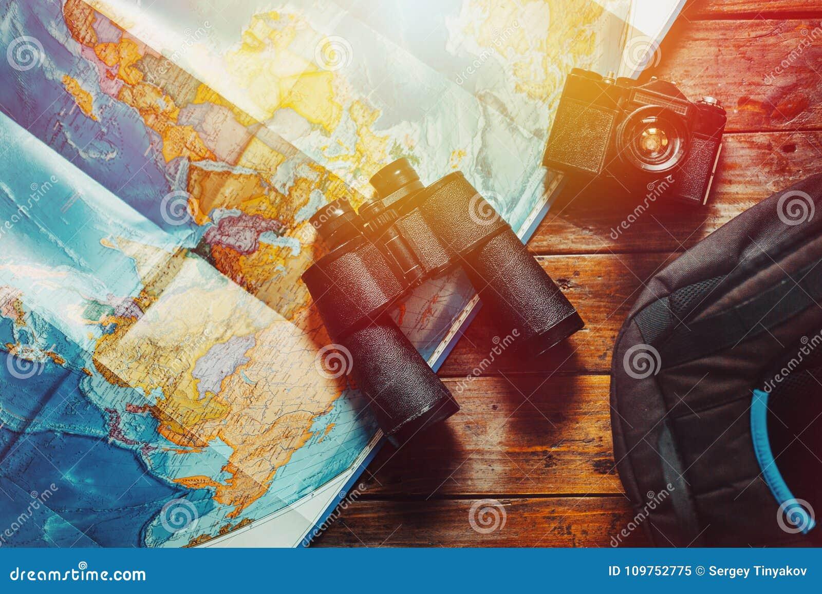 冒险发现侦察员旅途概念 减速火箭的影片照相机、地图、背包和双筒望远镜在木表,顶视图上