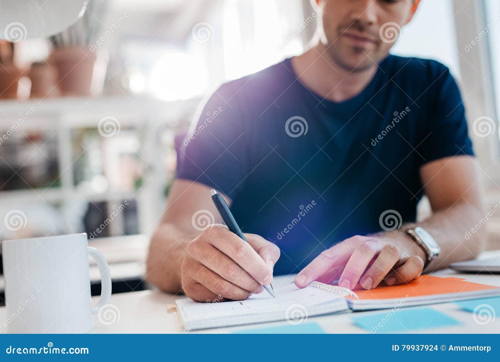 写下注意事项的商人在日志在他的书桌