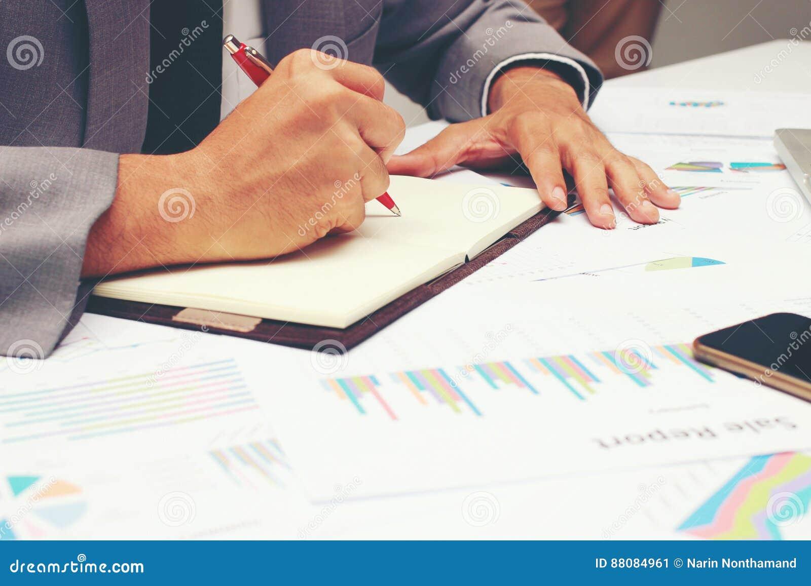 写业务报告的商人在有红色笔的空白的笔记本在书桌办公室 企业概念: