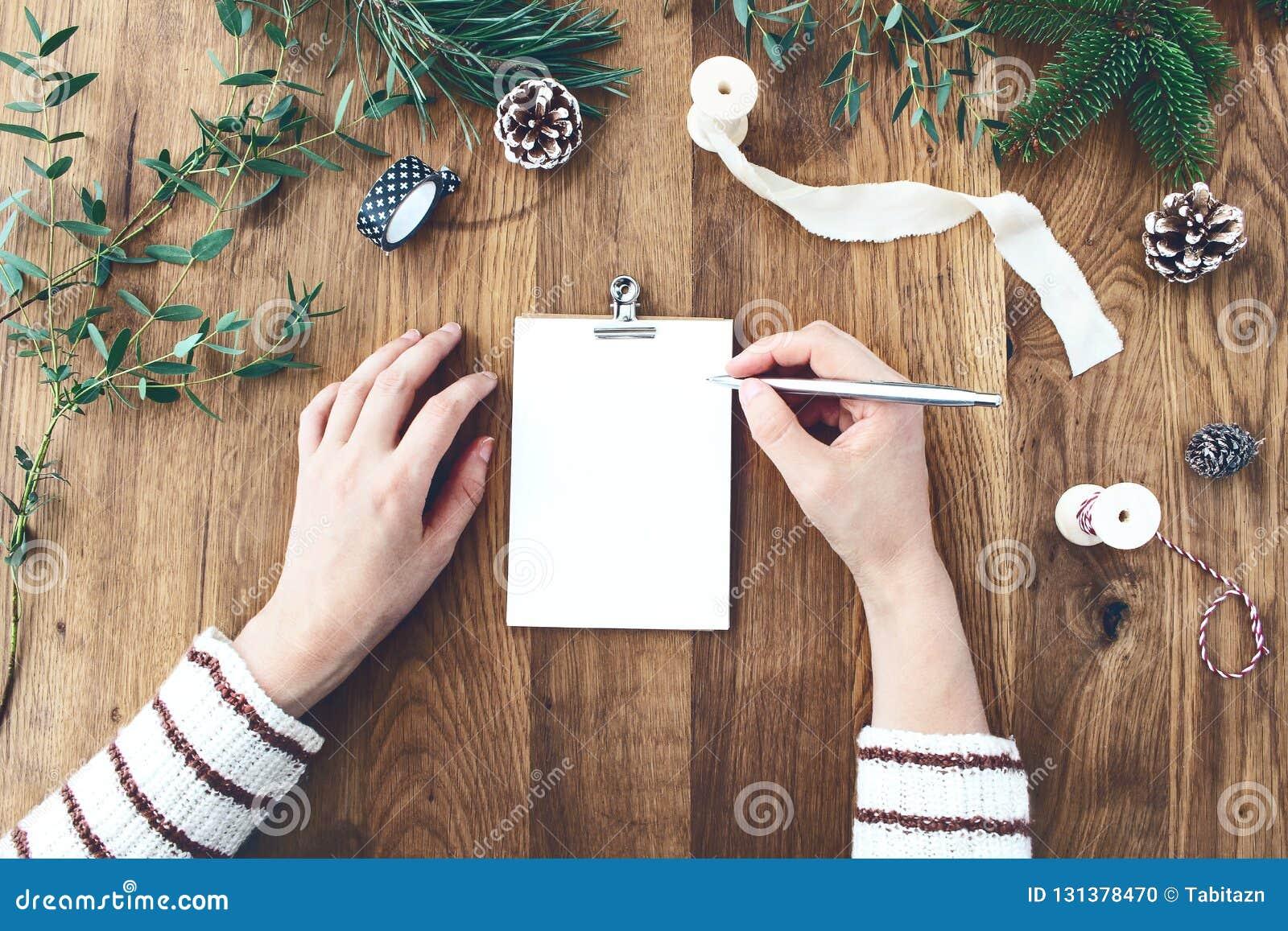 写圣诞节愿望,目标,对空的封缄信片的决议的妇女手 老与圣诞节的橡木木桌
