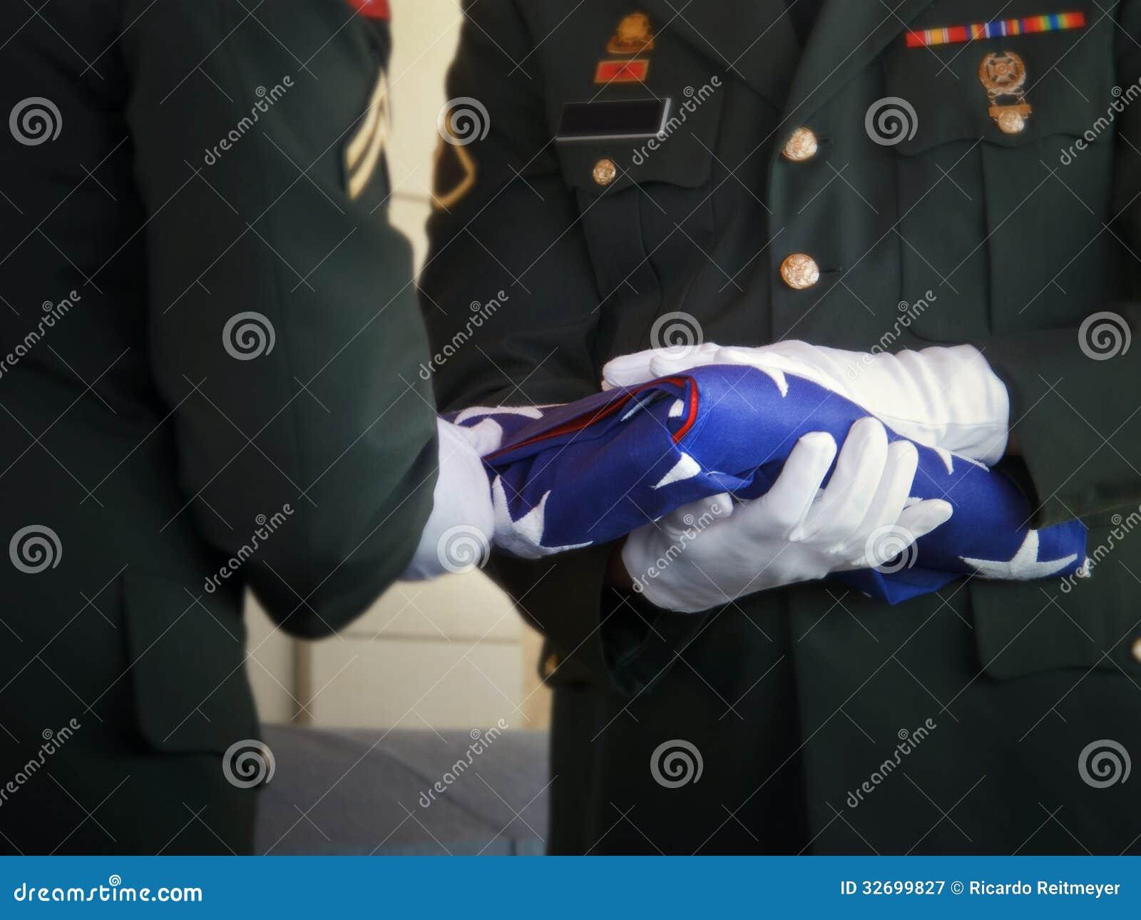 军事仪仗队折叠美国旗子在经验丰富的葬礼