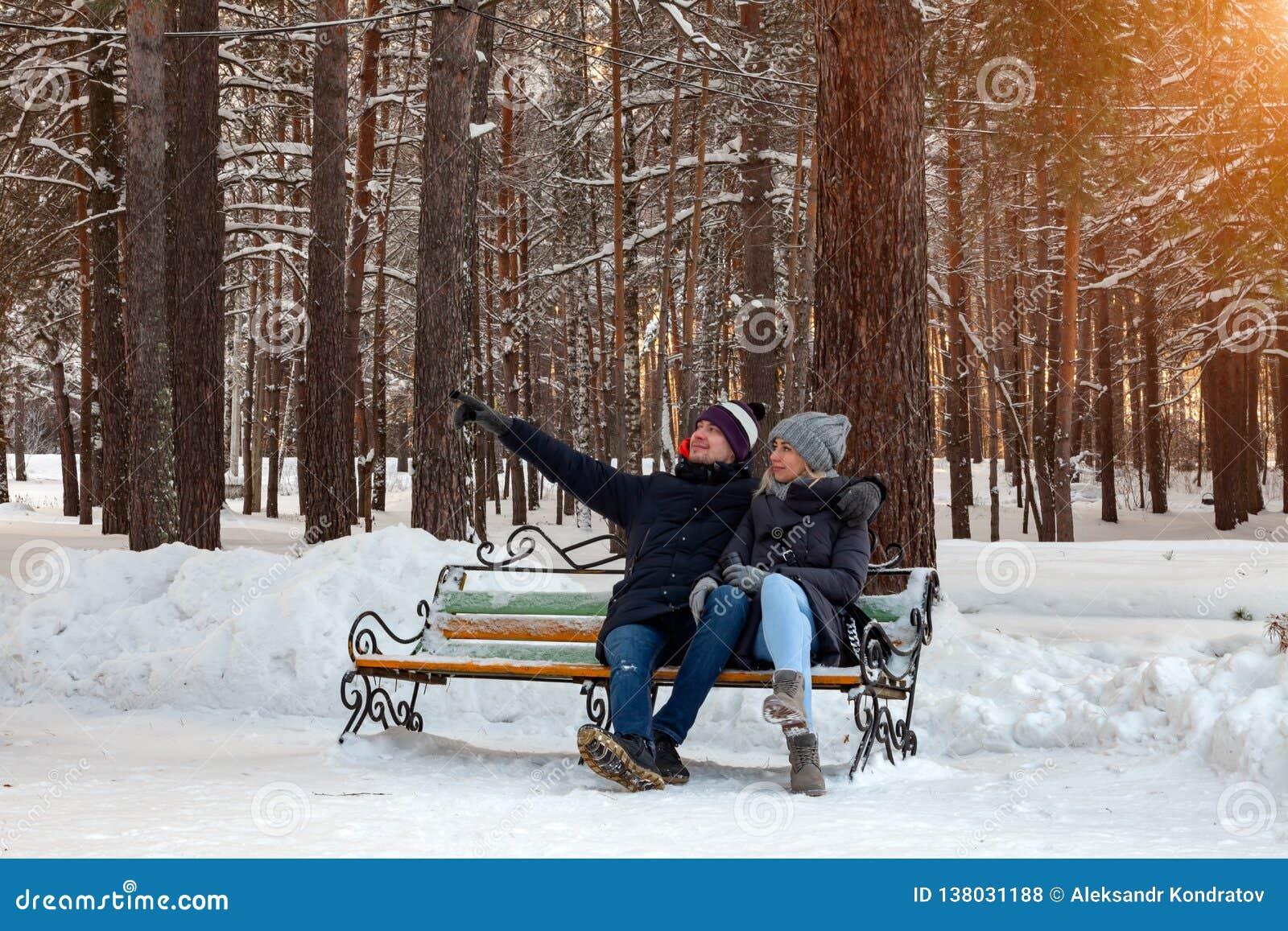 冬天下午,在夹克的一对爱恋的夫妇和帽子坐一条长凳在拥抱人展示的雪的森林