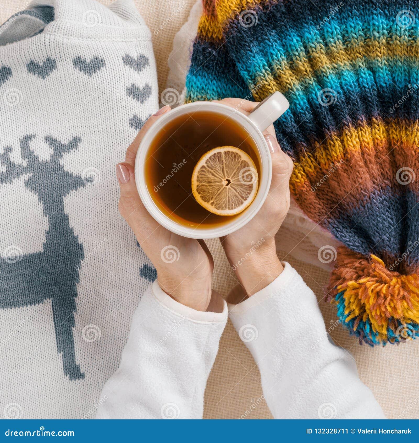 冬天来临,妇女的手拿着杯子热的茶用柠檬,背景是温暖的季节性衣裳,特写镜头视图从