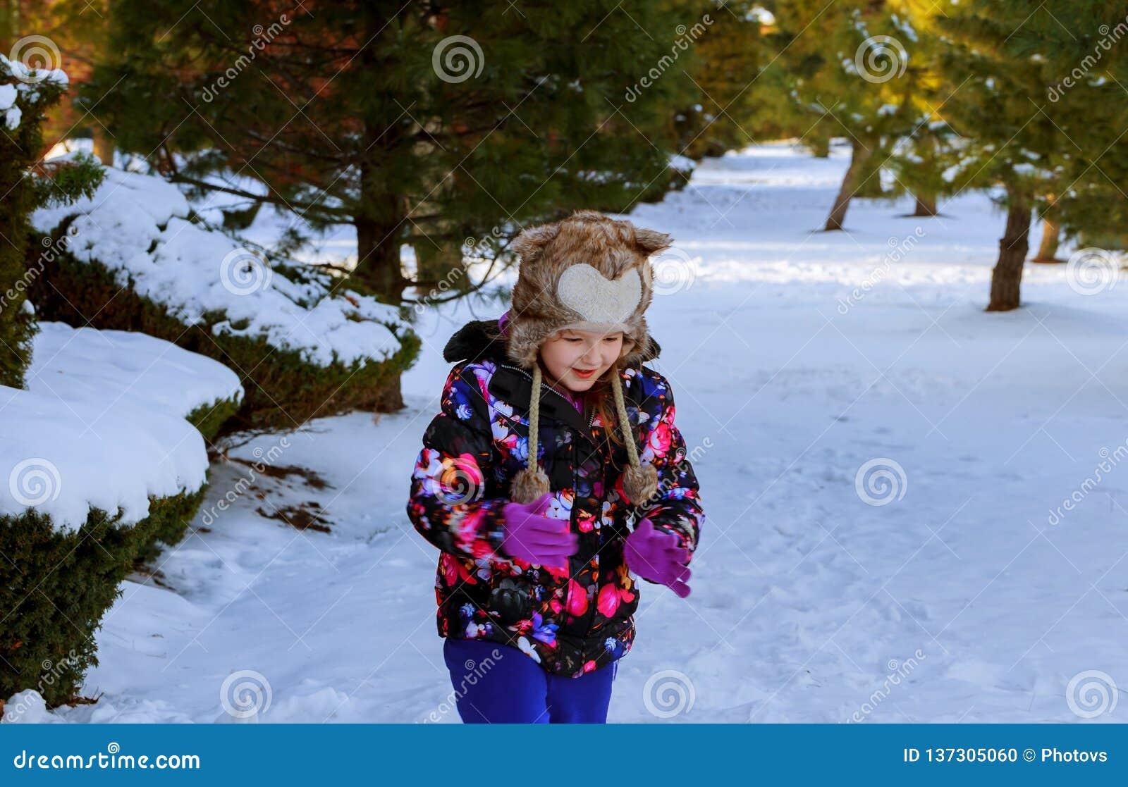 冬天衣裳的一个女孩跑到与一使用的雪小山在与雪的冬天