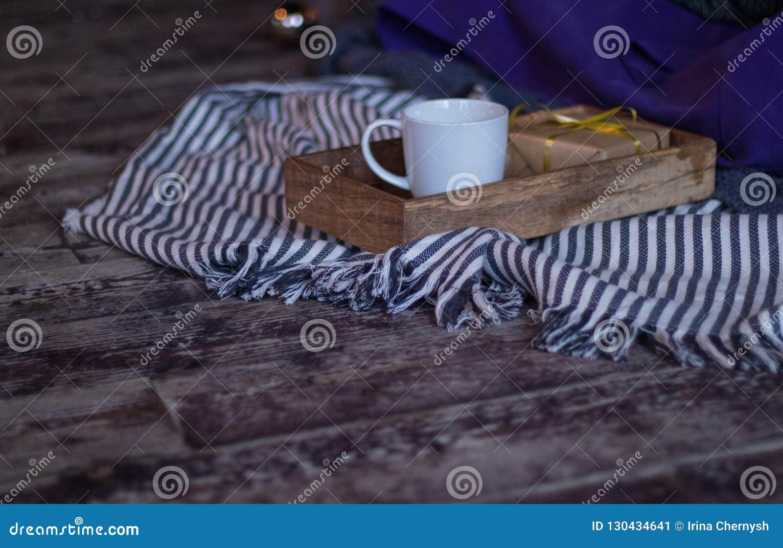 冬天装饰:咖啡、礼物、盘子、球和舒适镶边格子花呢披肩 所选的重点