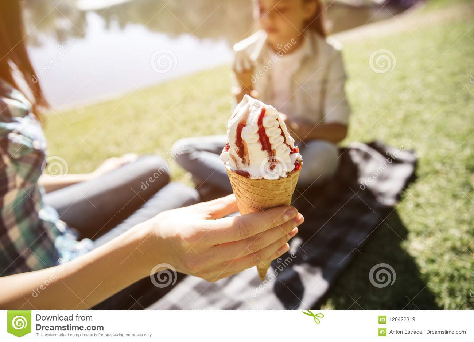 冰淇凌成人藏品骗局的好的图片在手中 有除icream以外成人和藏品骗局的女孩开会