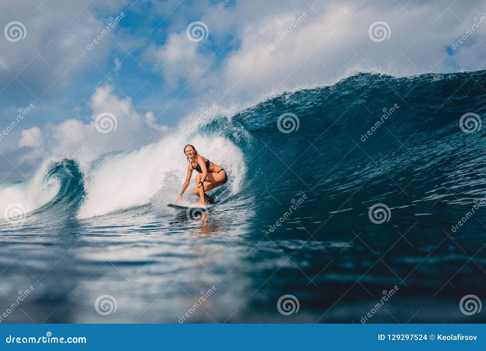 冲浪板的海浪女孩在桶波浪 妇女在冲浪期间的海洋