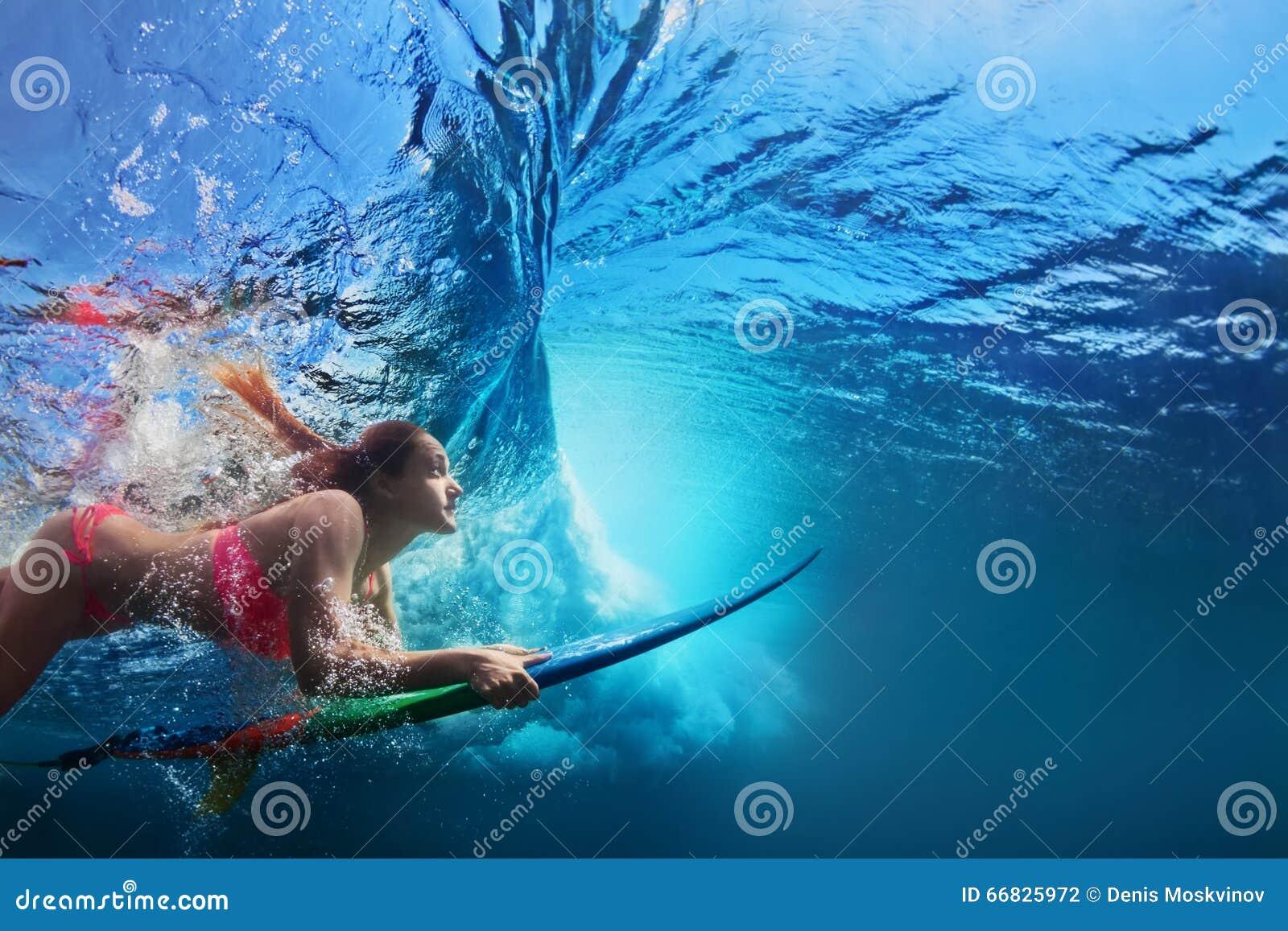 冲浪者在海浪下的女孩潜水水下的照片