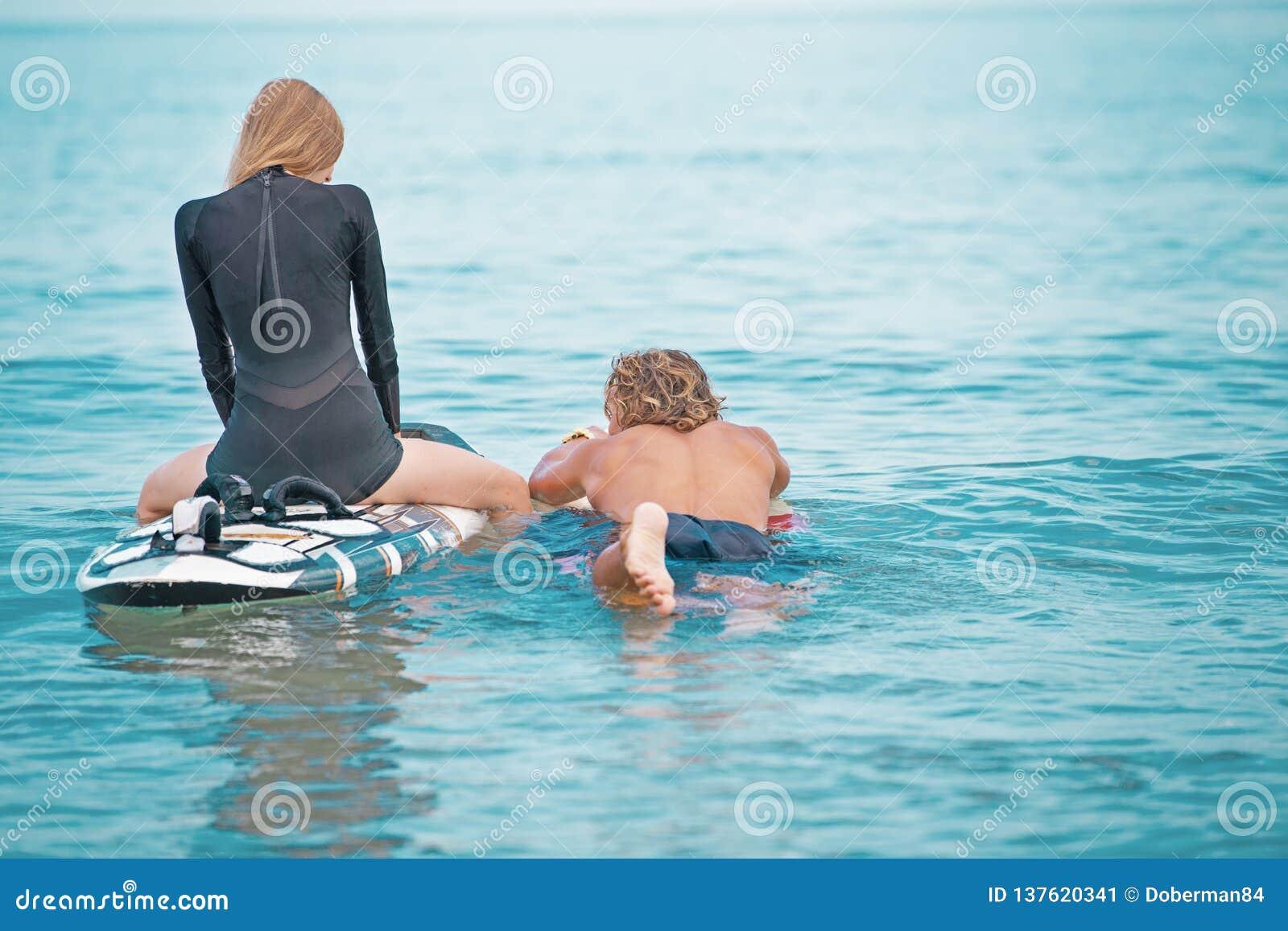 冲浪者海滩微笑的夫妇的冲浪者游泳和获得乐趣在夏天 极限运动和假期概念