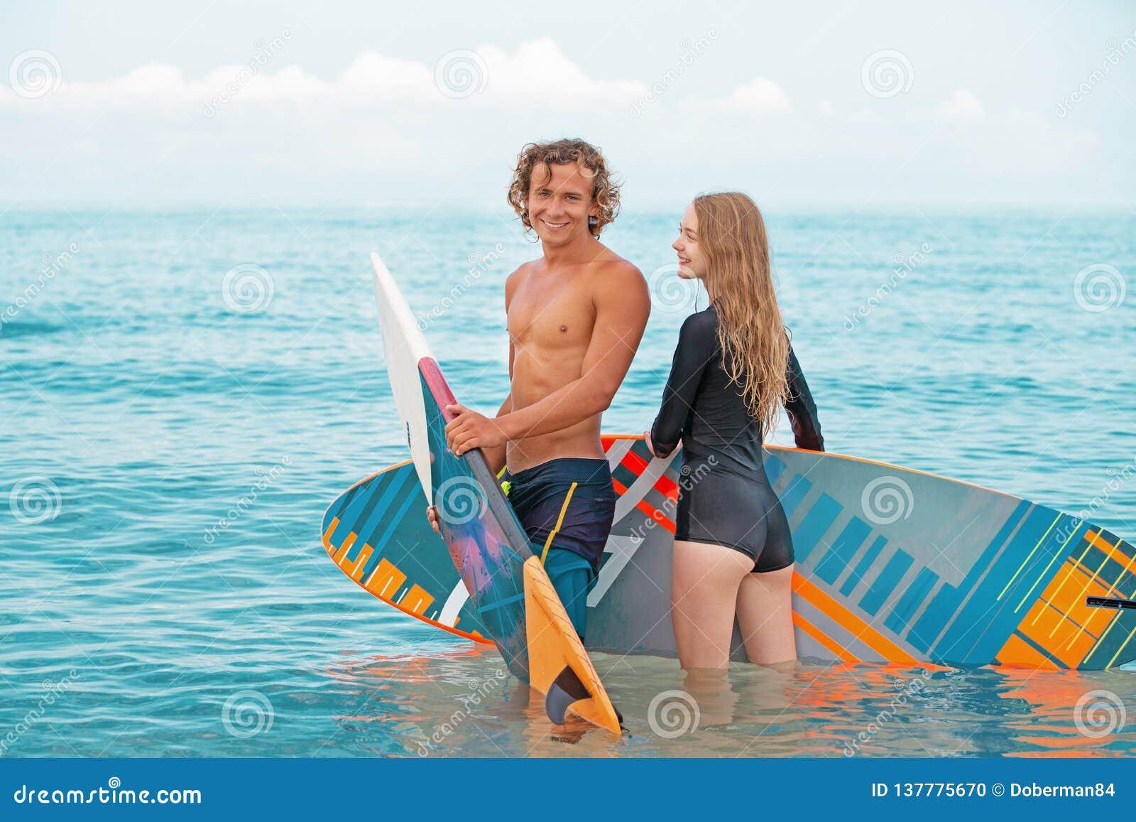 冲浪者海滩微笑的夫妇的冲浪者走在海滩和获得乐趣在夏天 极限运动和
