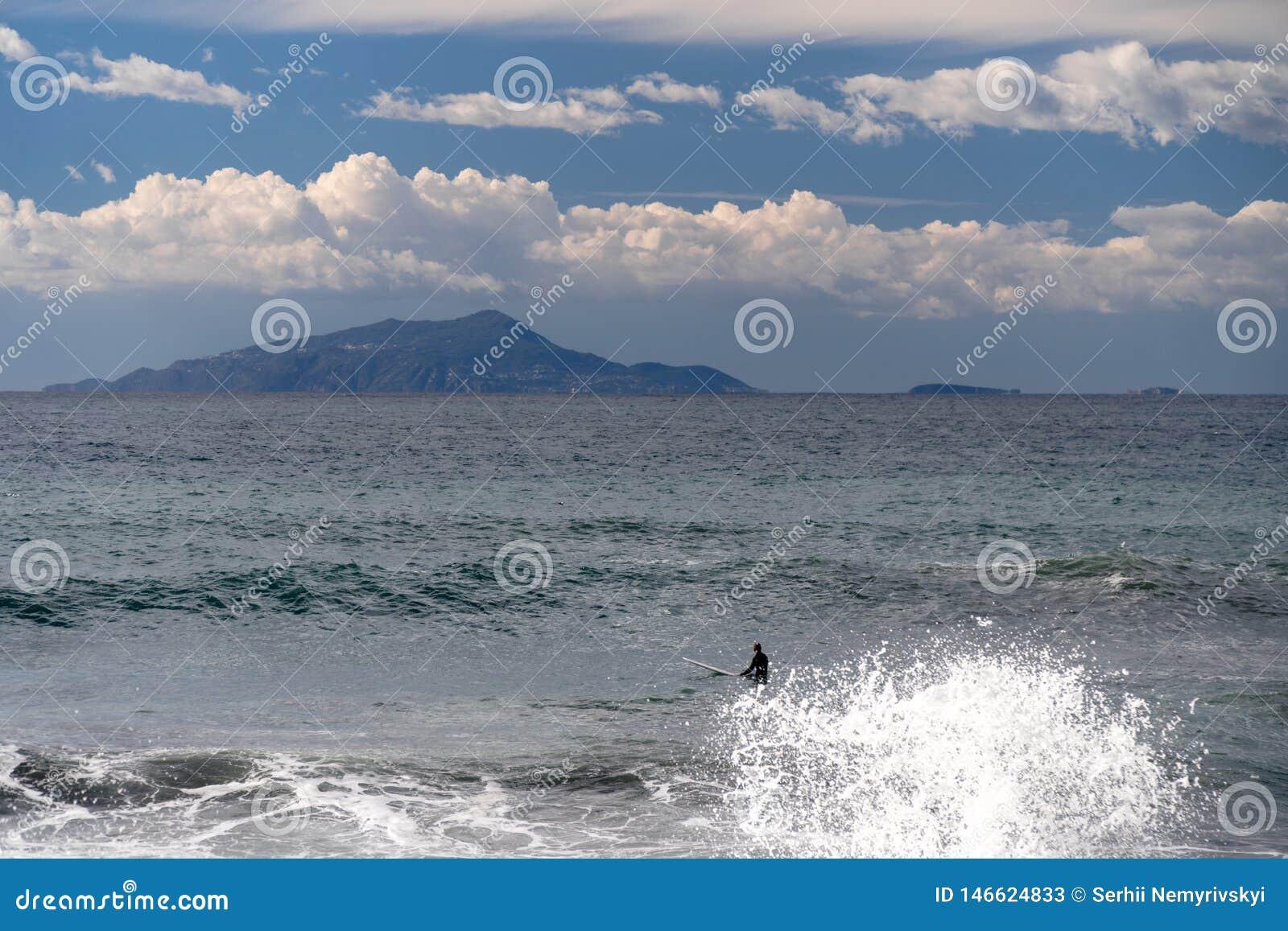冲浪者采取波浪,在冲浪板,沿波浪的幻灯片,在山的背景中,索伦托意大利