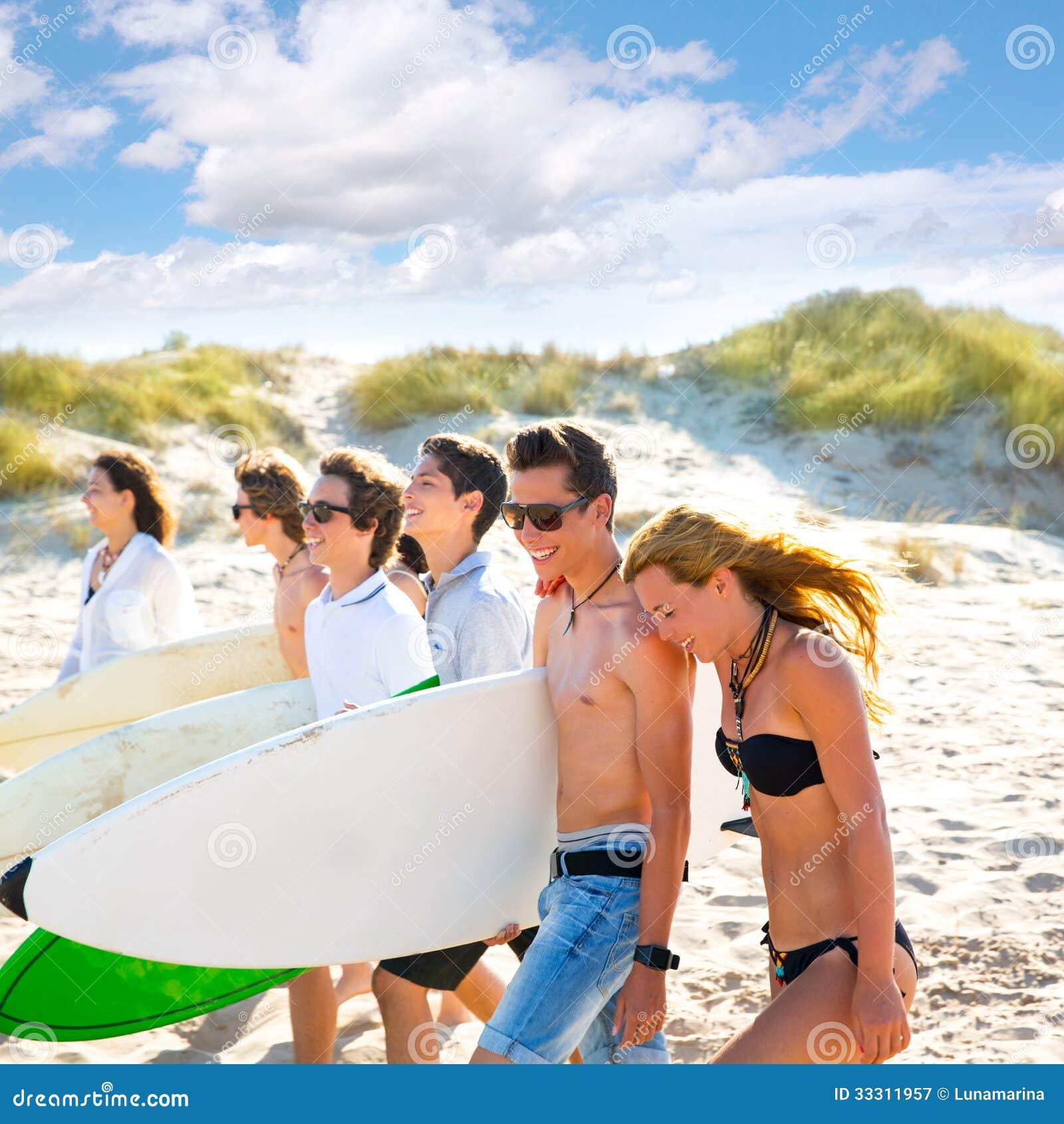 冲浪者青少年的男孩和女孩编组走在海滩