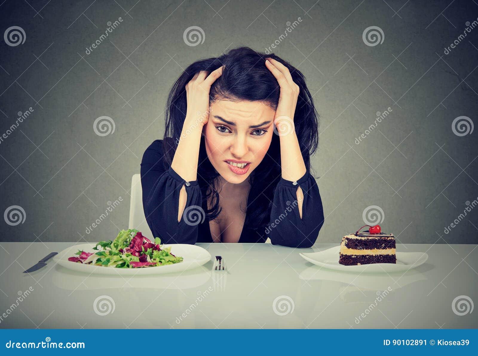 决定的妇女疲倦了于饮食制约吃她热衷的健康食物或蛋糕