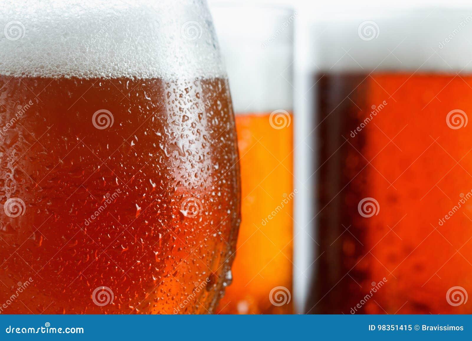 冷淡的杯凉快的啤酒起泡沫,用下落盖,特写镜头