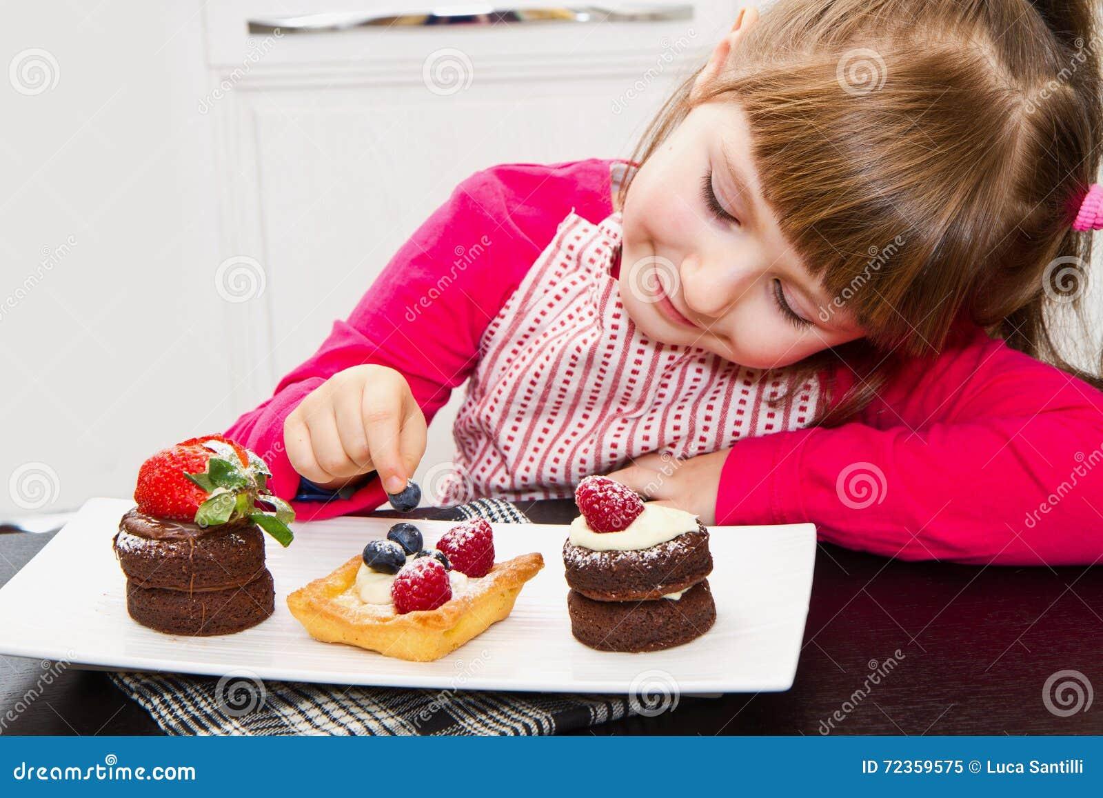 准备和吃蛋糕用果子的小女孩
