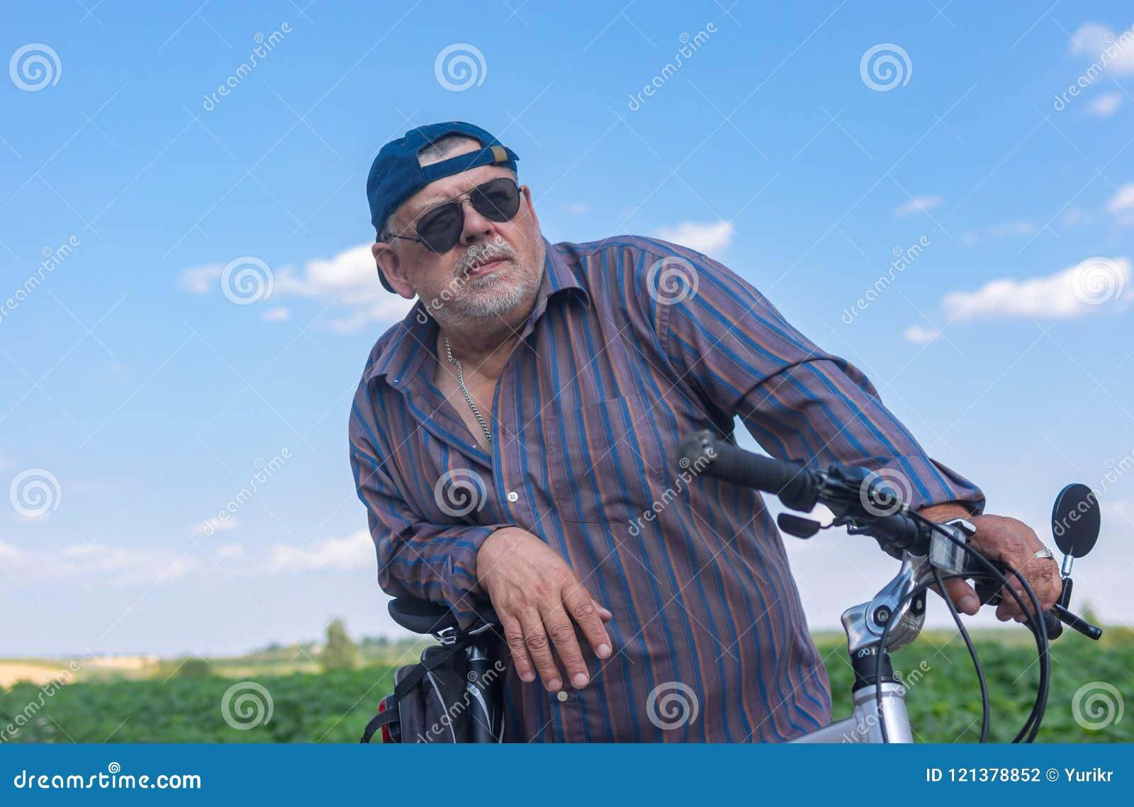 准备好一名有胡子,胖的老人的画象对在自行车的夏天乘驾