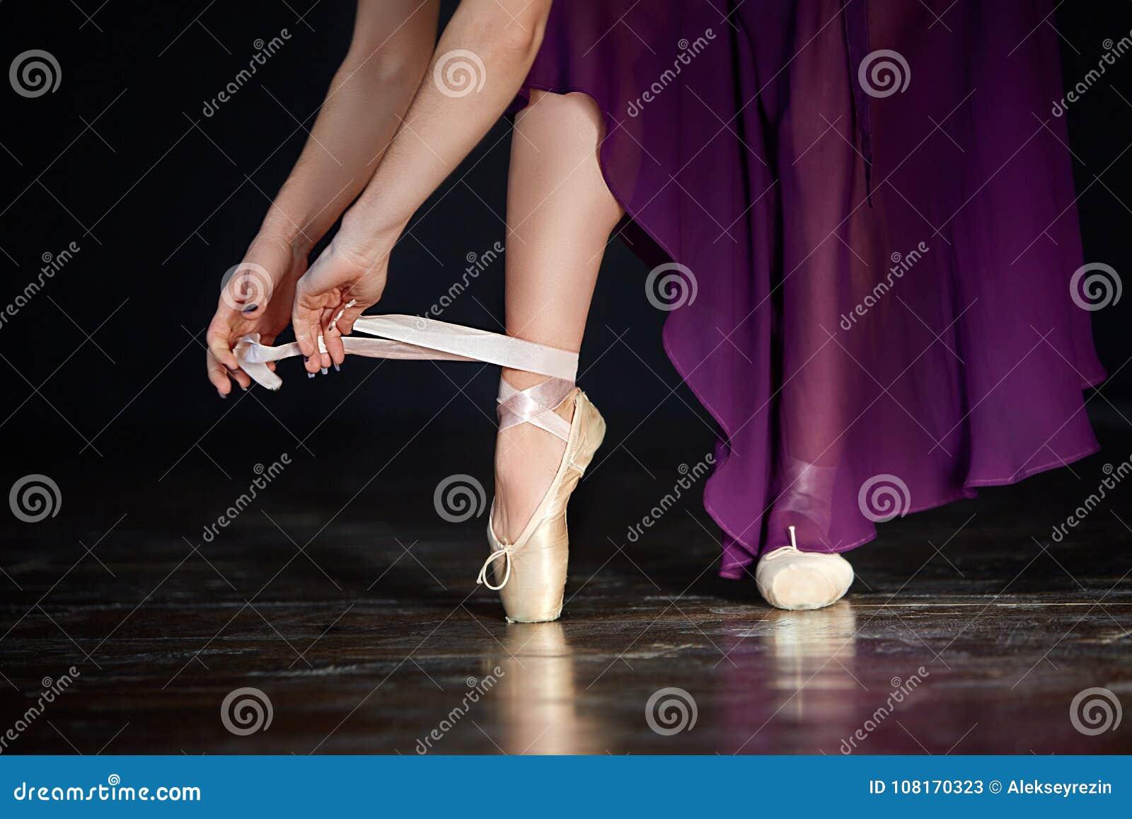 准备好年轻的芭蕾舞女演员一个古典舞蹈 女孩佩带的点穿上鞋子在黑暗的背景的特写镜头