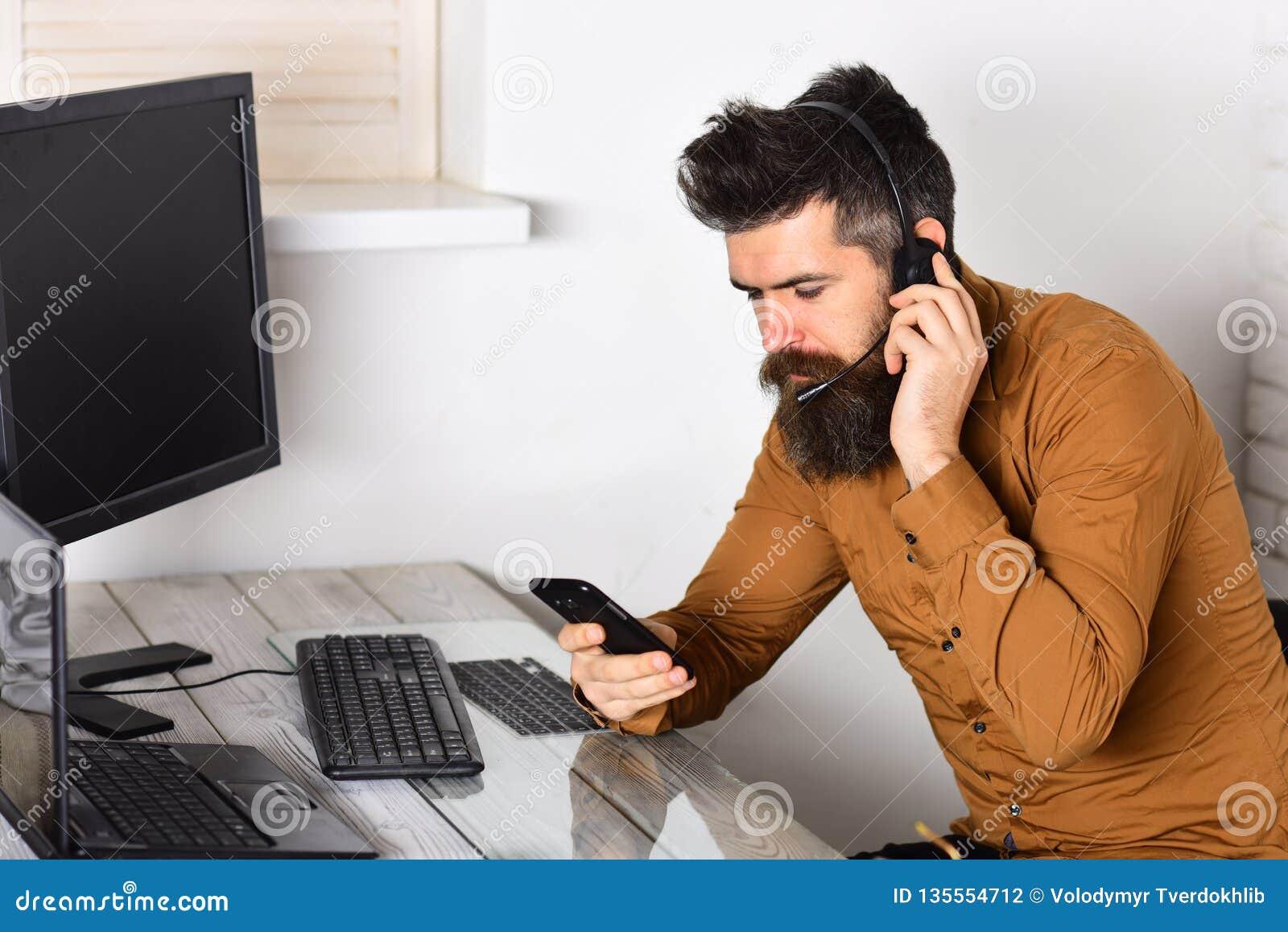准备帮助 呼叫中心运算符在工作 工作在办公室的有胡子的人 有长的胡子和耳机的人 博若莱红葡萄酒