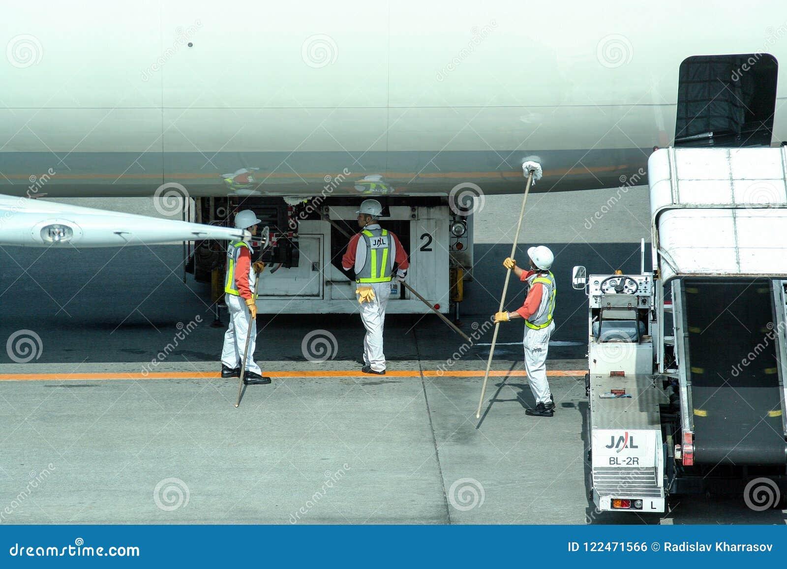 准备飞机的工作者对飞行 在登巴萨机场