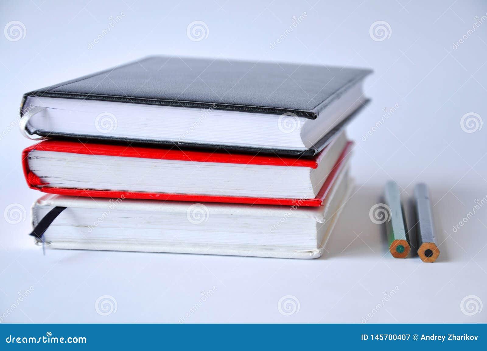 几个书或笔记本在一张桌上在白色背景