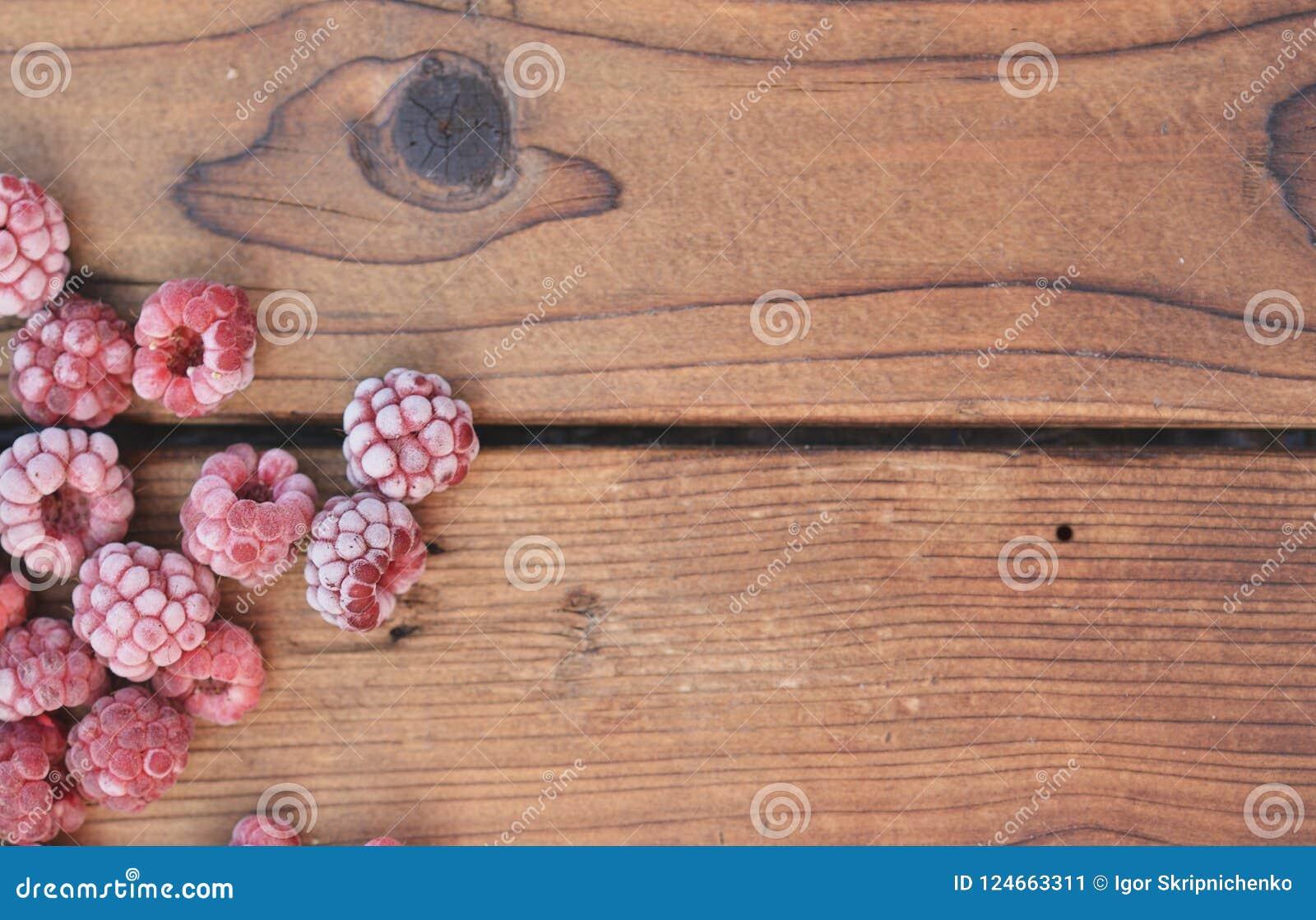 几个冷冻莓,盖用果子,在木背景说谎