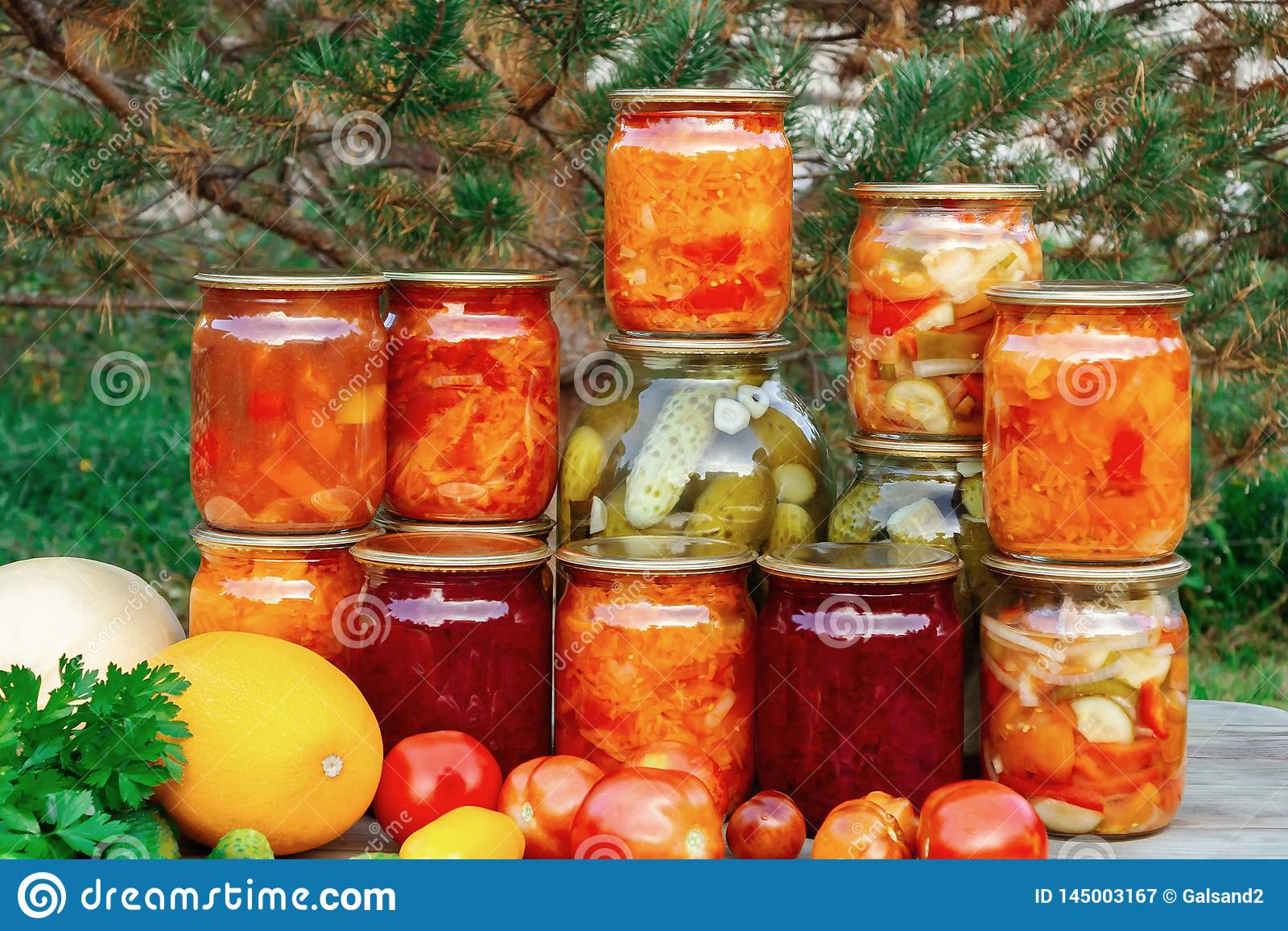 几个自创瓶子罐装菜和新鲜蔬菜在一张木桌-图象上