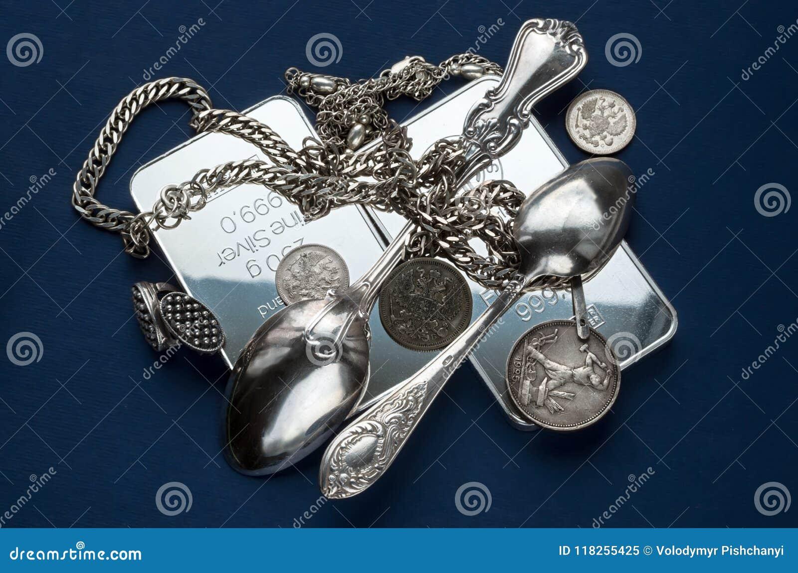 几个银块、银器、jewelery和老银币在深蓝背景