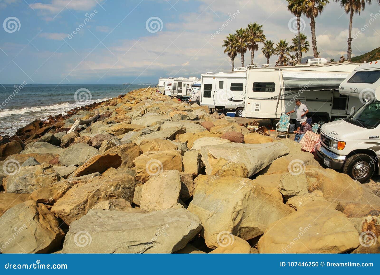 几围拢的两个人在Faria多岩石的海滩的RVs