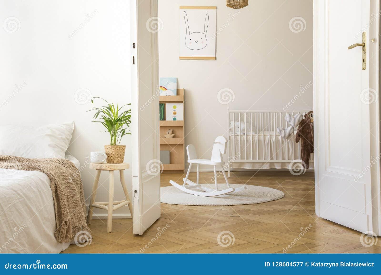 凳子的植物在白色卧室内部的床旁边与在地毯和摇篮的摇马