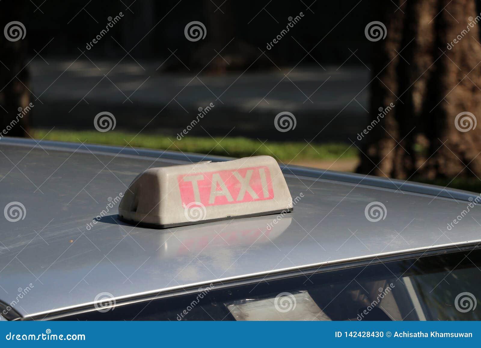 出租汽车光标志或小室标志在土褐色的白色和红色与白色文本在汽车屋顶在街道被弄脏的背景