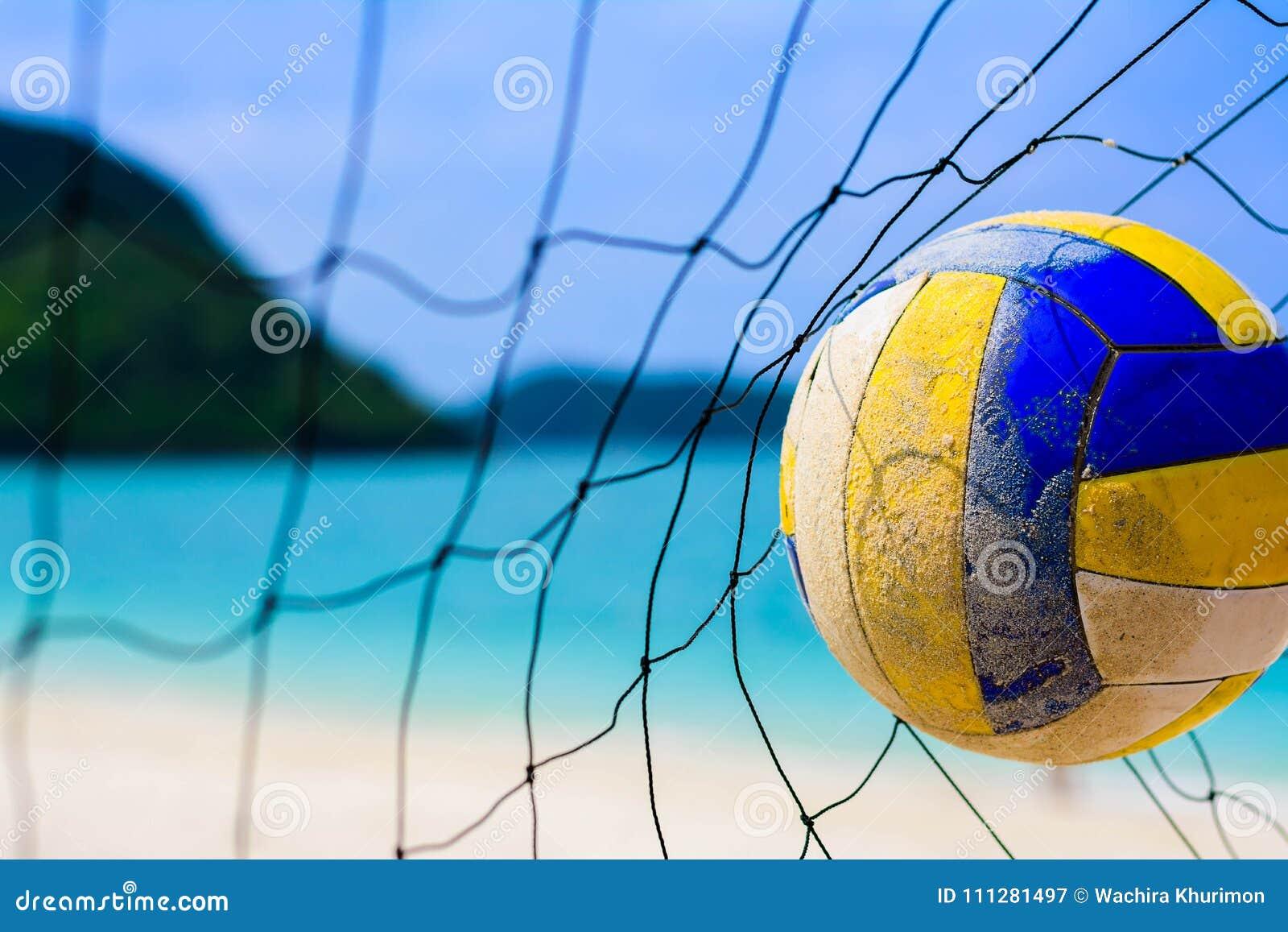 击中对在迷离海滩和蓝色海的网的排球