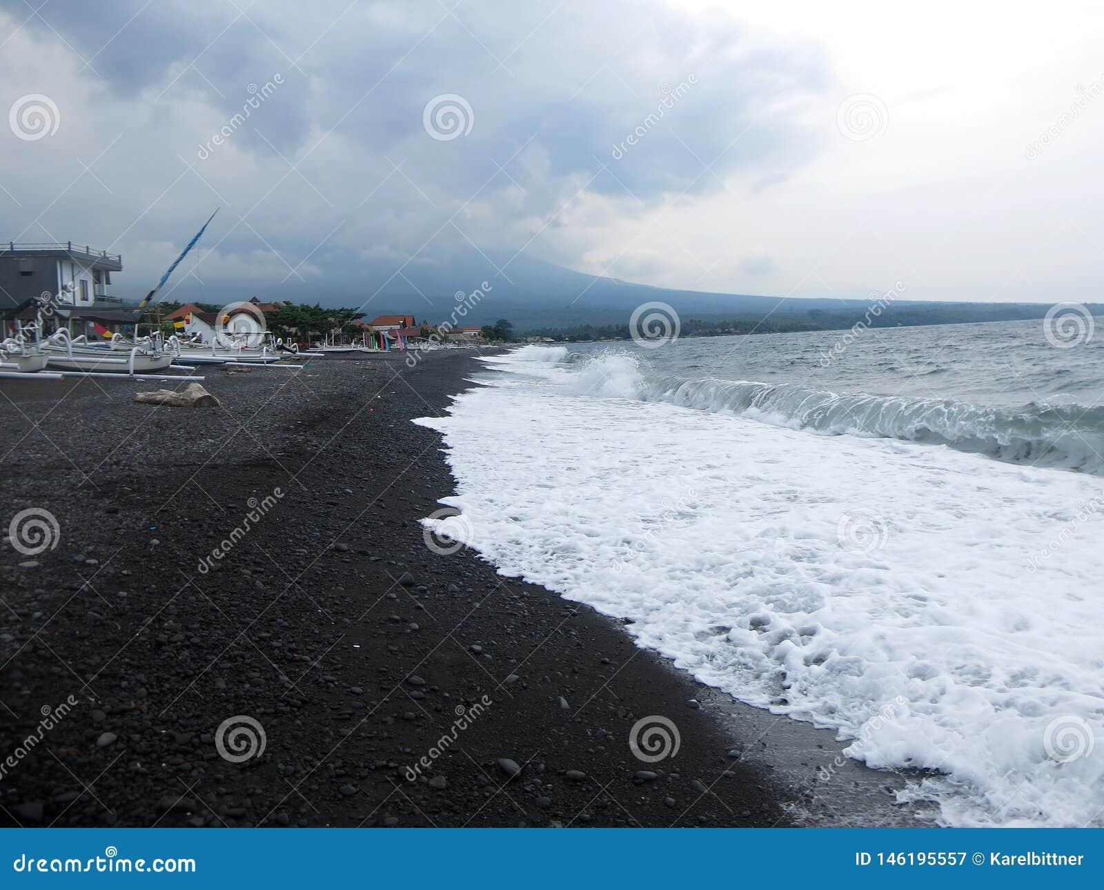 击中巴厘岛的含沙黑火山的沙滩波浪、海浪和海泡沫 在Amed,海是安静,但是在附近的波浪