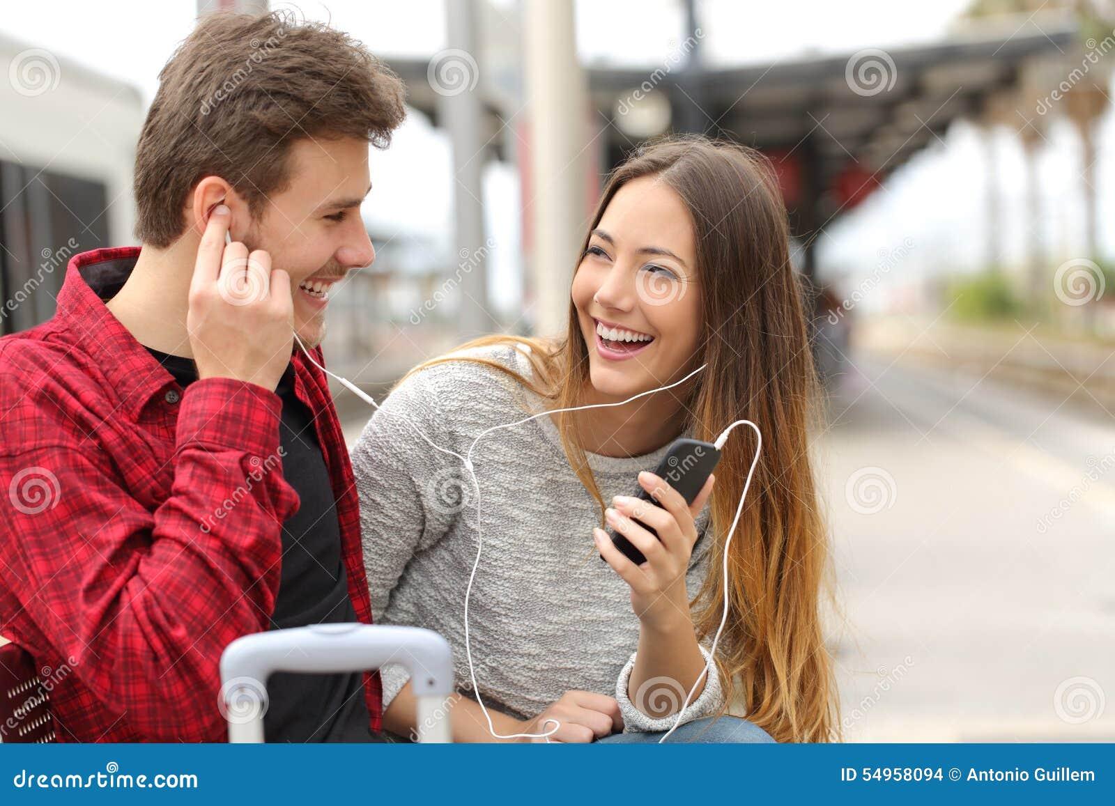 分享音乐的旅客愉快的夫妇在度假