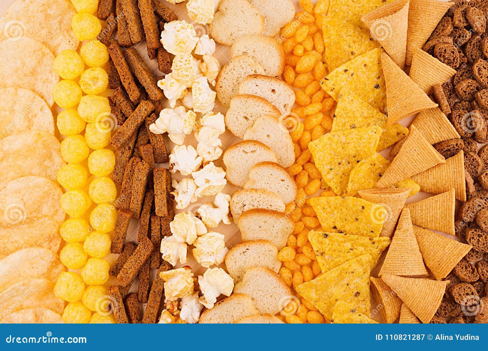 分类嘎吱咬嚼的快餐-玉米花,烤干酪辣味玉米片,油煎方型小面包片,玉米黏附,土豆片作为装饰背景,顶视图,特写镜头