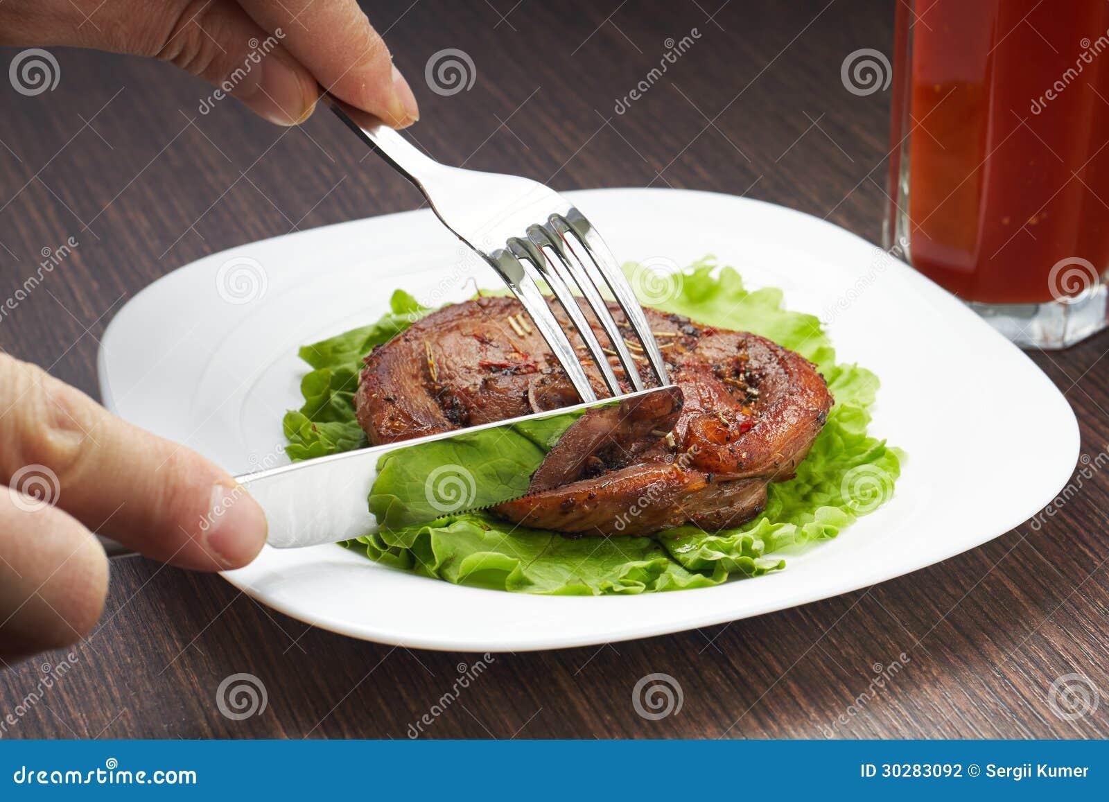 切与刀子的烤牛排在白色板材