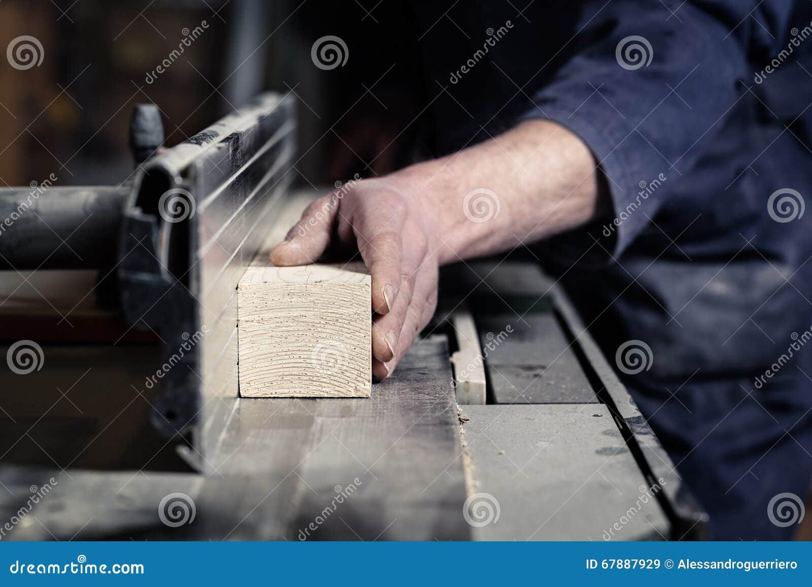 切开与Tablesaw的木匠的手木头