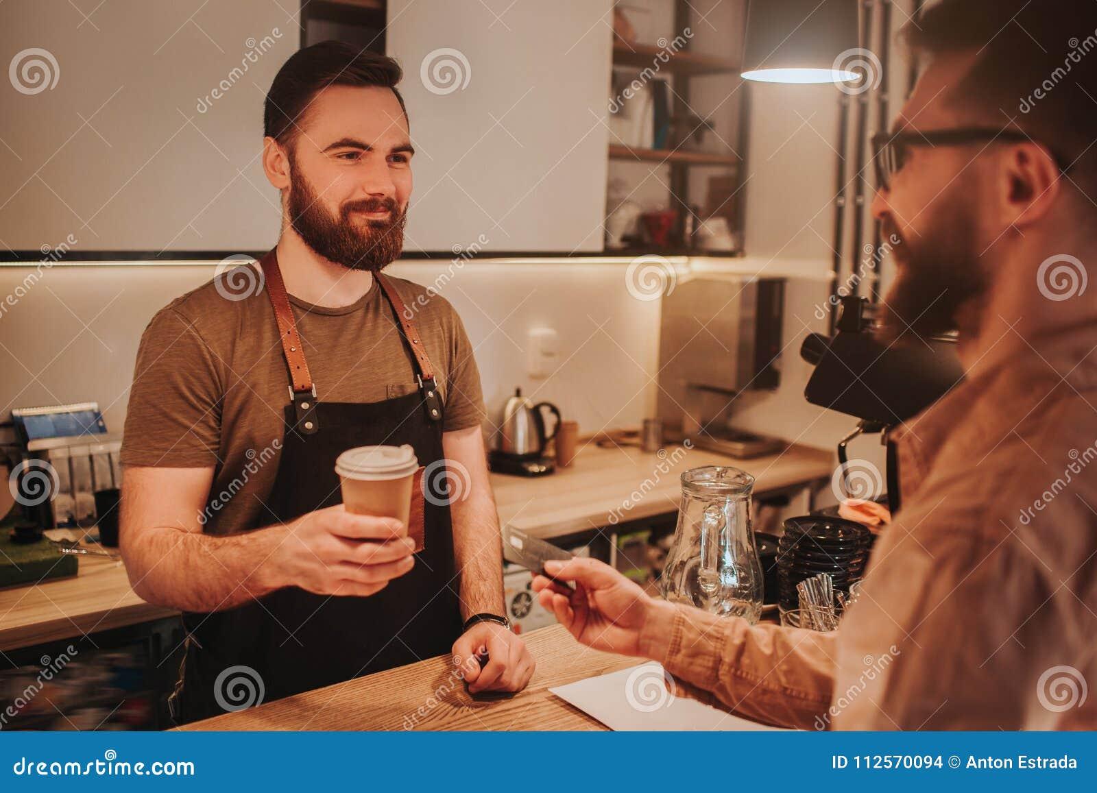 切开在酒吧` s桌后的男服务员穿戴围裙的看法和身分和给一杯咖啡顾客 在